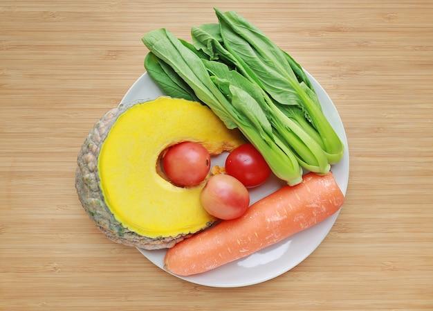 Variété de légumes frais sur une plaque blanche sur fond de planche de bois.