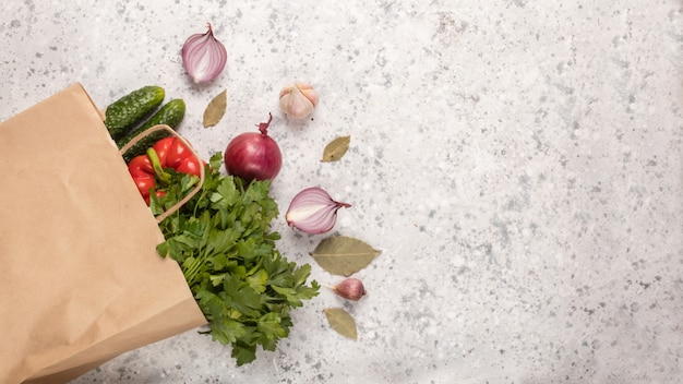 Variété de légumes frais et de verdure dans un sac écologique en coton sur béton