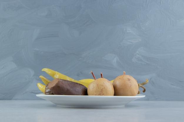 Variété de légumes et de fruits fermentés sur plaque blanche.