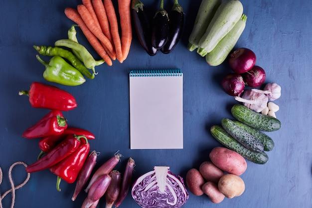 Variété de légumes isolés sur table bleue avec un livre de recettes au milieu.