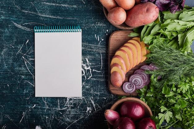 Variété de légumes isolés sur table bleue avec un livre de recettes de côté.
