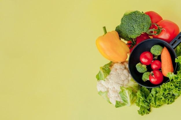 Variété de légumes et poêle sur un tableau noir, vue de dessus. concept végétalien et sain.