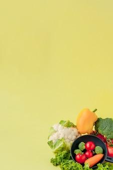 Variété de légumes et poêle sur un tableau noir, vue du dessus. concept végétalien et sain.
