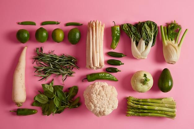 Variété de légumes verts, de fruits et d'herbes. nourriture végétalienne biologique. deux types de choux, d'asperges et de verdure sur une surface rose.