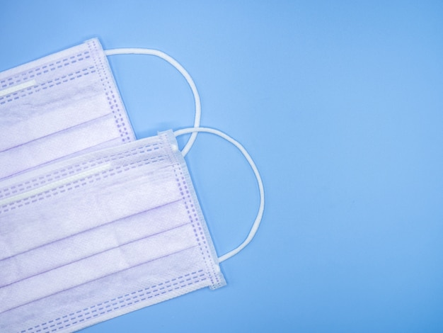 Variété de masques sur fond bleu avec espace de copie pour le texte comme outil de prévention primaire lors de l'épidémie de covid-19 ou de la pollution de la pollution de l'après-midi 2,5. auto-isolement, coronavirus, covid-19 et concept médical