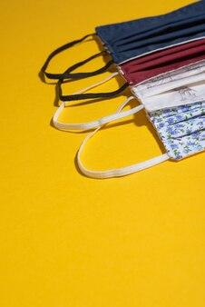 Variété de masques hygiéniques sur bureau jaune close up