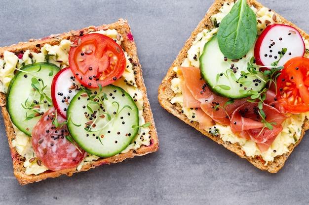 Variété de mini sandwichs avec fromage à la crème, légumes et salami. sandwichs au concombre, radis, tomates, salami sur fond gris, vue de dessus. mise à plat.