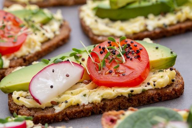 Variété de mini sandwichs avec fromage à la crème, légumes et salami. sandwichs au concombre, radis, tomates, salami sur fond gris, vue du dessus. mise à plat.