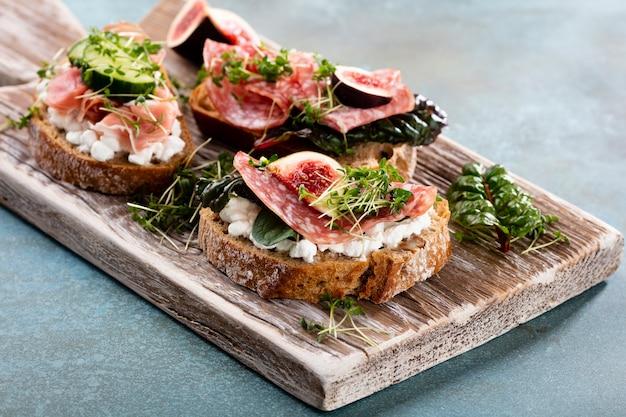 Variété de mini sandwichs avec légumes au fromage à la crème et salami