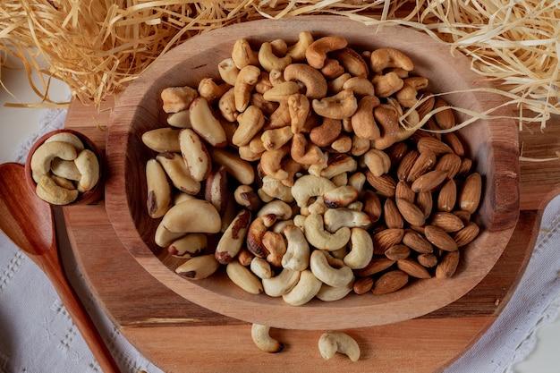 Variété de noix dans un bol en bois et dans deux tasses en bois avec fond de paille. principales noix de la cuisine brésilienne.