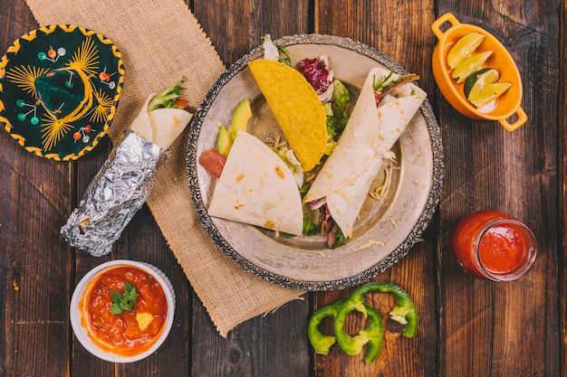 Variété de nourriture mexicaine avec un chapeau sur une table en bois