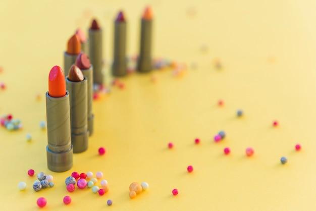 Variété de nuances de rouge à lèvres disposées en rangées sur fond jaune