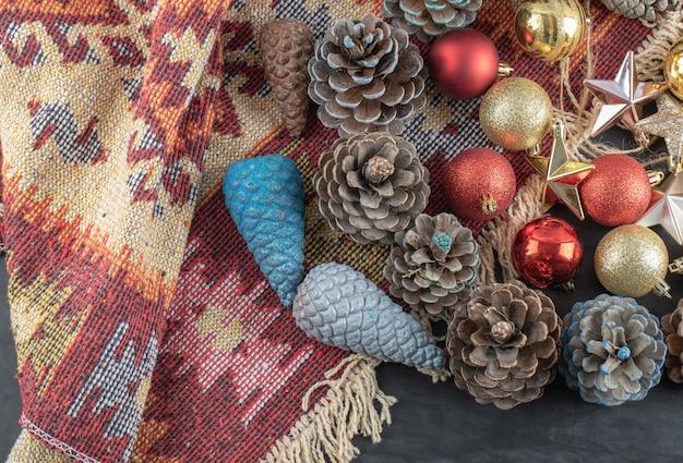 Variété d'ornements d'arbre de noël sur un morceau de tapis ethnique à motif rouge