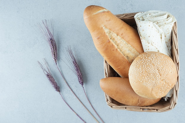 Variété de pain dans le panier et de blé sur la surface de la pierre