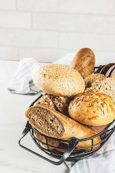 Variété de pain frais fait maison, dans un panier en métal, fond en marbre blanc