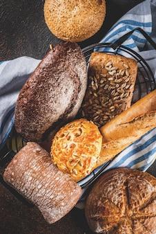 Variété de pain frais fait maison, dans un panier en métal, fond rouillé foncé vue de dessus