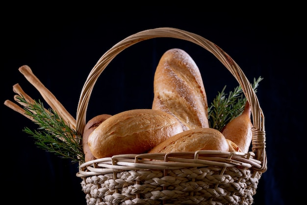 Variété de pains dans le panier sur la table en bois dans l'obscurité