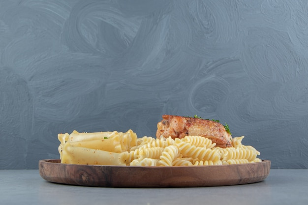 Variété de pâtes au poulet grillé sur plaque de bois.