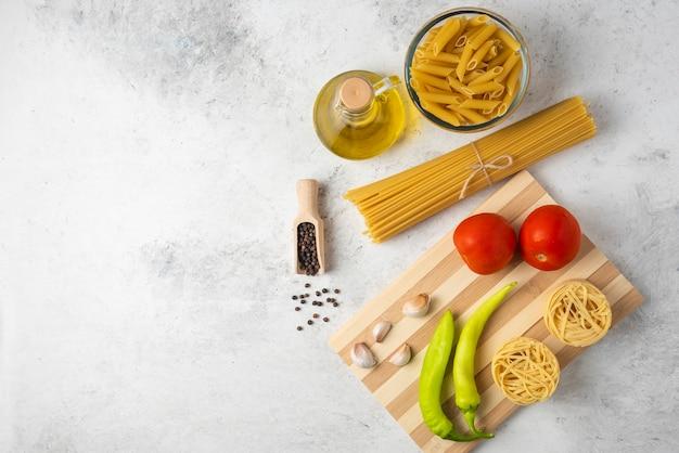 Variété de pâtes crues, bouteille d'huile d'olive, grains de poivre et légumes sur tableau blanc.