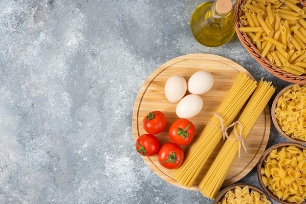 Variété de pâtes crues avec des œufs, des tomates fraîches et une bouteille d'huile sur une surface en marbre.