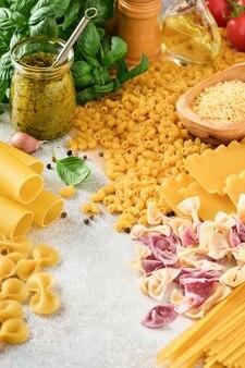 Variété de pâtes italiennes traditionnelles: spaghettis colorés, tagliatelles, farfalle, penne, ptititm, nouilles, fusilli, cannelloni