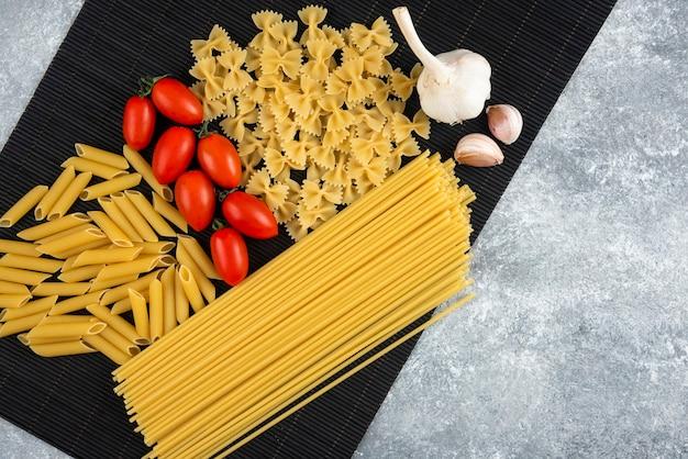 Variété de pâtes et légumes crus sur feuille de bambou noir.
