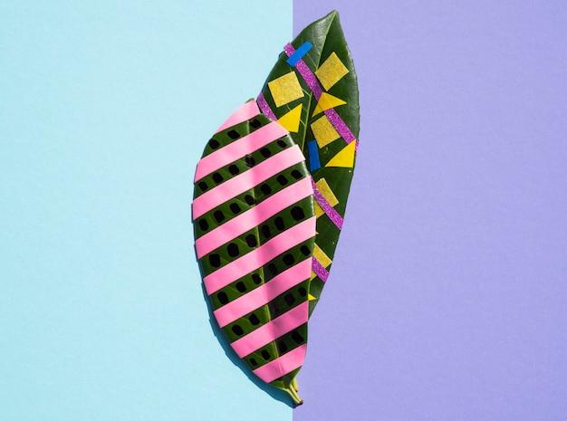 Variété de peintures et d'articles de papeterie sur des feuilles de ficus