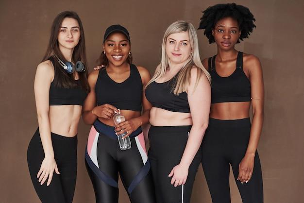 Variété de personnes. groupe de femmes multiethniques debout contre l'espace brun