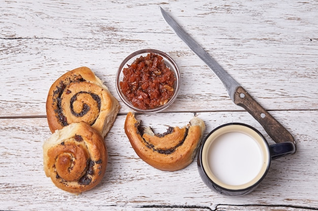 Variété de petits pains feuilletés faits maison à la cannelle servis avec une tasse de lait, de la confiture, du beurre comme petit-déjeuner sur un fond en bois de planche blanche.