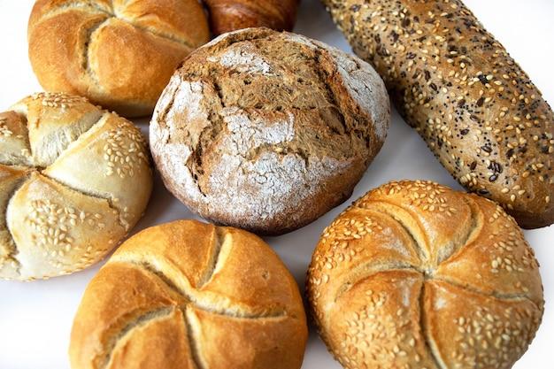 Variété de petits pains kaiser, croissant et baguette isolé sur fond blanc