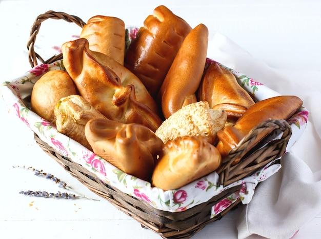 Variété de petits pains sucrés dans un panier en osier sur table