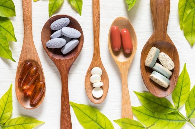Variété de pilules de vitamines à la cuillère en bois sur un fond blanc avec une feuille verte