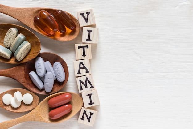 Variété de pilules de vitamines à la cuillère en bois sur fond blanc, produit complémentaire et de soins de santé