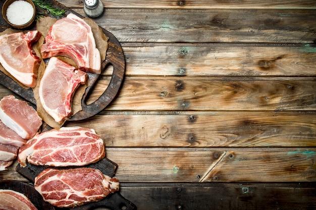 Variété de porc cru. sur un fond en bois.