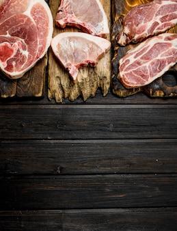Variété de porc cru sur table en bois.
