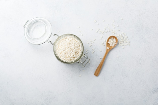 Variété de riz blanc brut arborio pour les plats de risotto italiens en bocal en verre sur béton blanc ou pierre.