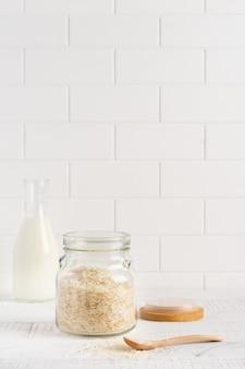Variété de riz blanc cru arborio pour les plats de risotto italien dans un bocal en verre sur fond de béton ou de pierre blanc. mise au point sélective. copiez l'espace.