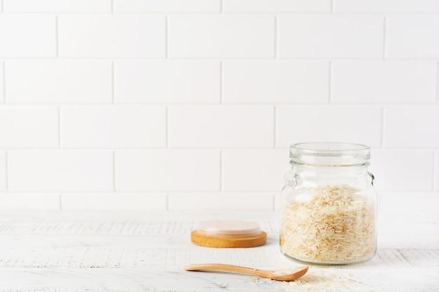 Variété de riz blanc cru arborio pour les plats de risotto italien dans un bocal en verre sur fond de béton ou de pierre blanc. mise au point sélective.