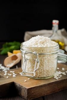 Variété de riz blanc cru arborio pour les plats de risotto italien dans un bocal en verre sur fond de bois foncé