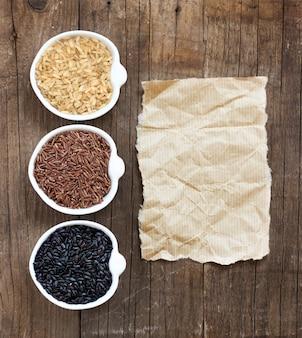 Variété de riz dans des bols à côté de l'ancien espace de copie papier sur la vue de dessus de table en bois