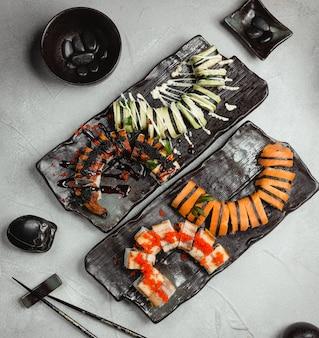 Variété de rouleaux sur des assiettes en pierre noire avec des baguettes noires.