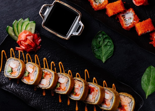 Variété de rouleaux de sushi en plaque noire avec sauce soja.