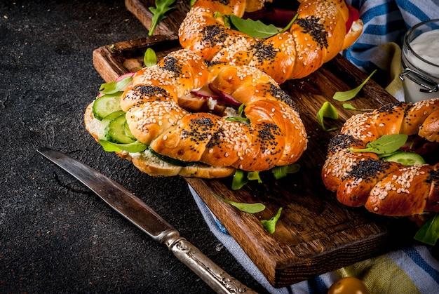 Variété de sandwichs bagels faits maison avec graines de sésame et de pavot, fromage à la crème, jambon, radis, roquette, tomates cerises, concombres, sur planche à découper. surface en béton foncé au-dessus