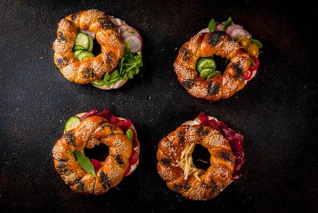 Variété de sandwichs bagels faits maison avec graines de sésame et de pavot, fromage à la crème, jambon, radis, roquette, tomates cerises, concombres, surface en béton foncé au-dessus