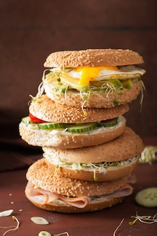 Variété de sandwichs sur bagels: œuf, avocat, jambon, tomate, fromage à pâte molle, germes de luzerne
