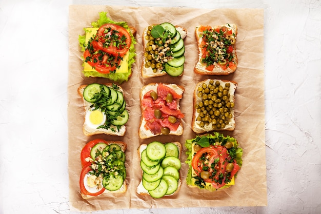 Une variété de sandwichs avec du fromage à la crème, du saumon, des œufs, des herbes et des légumes sur du papier kraft