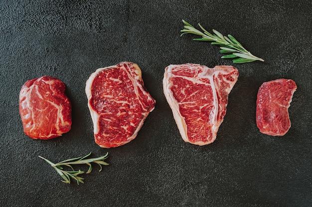 Variété de steaks de boeuf sur une surface sombre