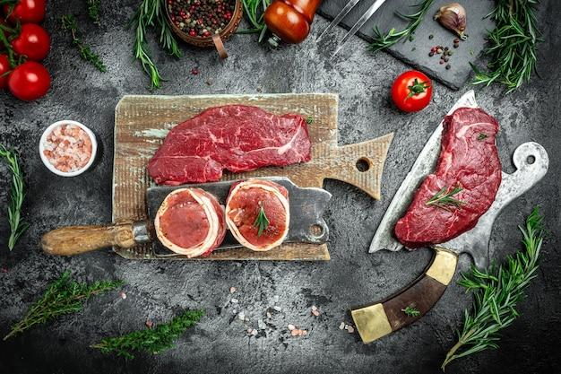 Variété de steaks de viande crue black angus prime steak de rumsteck de boeuf, filet mignon de filet mignon pour griller sur un vieux couperet à viande sur fond sombre. bannière, vue de dessus de recette de menu.