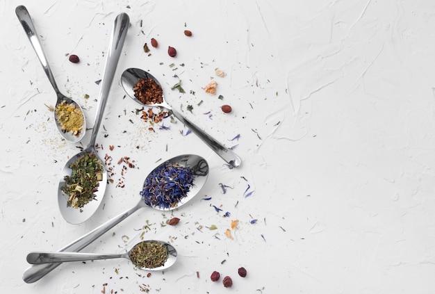 Variété de thé séché, de fines herbes séchées, de thé vert et de fruits sur des cuillères.