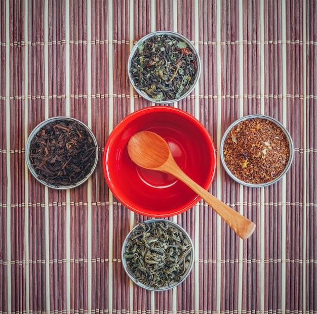 Une variété de thés et une cuillère en bois dans une tasse rouge vide sur une natte de bambou